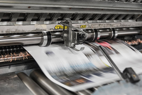 newspaper printing press working at speed