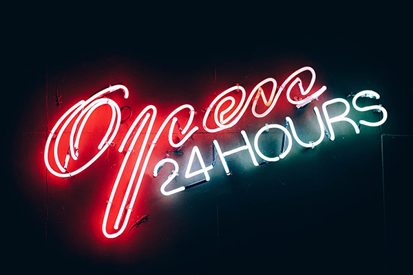 NEon light in red and white, reads 'Open 24 hours'